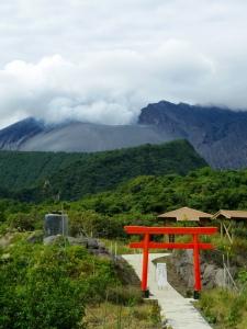 Ein 鳥居 (Torii) auf 桜島 (Sakurajima). Im Hintergrund ein aktiver Vulkan.